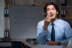 Ночь молодого мужского архитектора работая на офисе стоковые фото