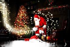 Ночь рождества, Санта Клаус кладет подарки стоковое фото