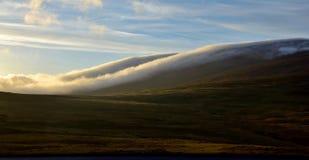 Ночь середины лета в Исландии Облака плавают вниз с горы стоковое изображение rf