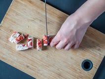 Нуга клубники отрезка рук надземного взгляда женская с ножом на деревянной доске Стоковое Изображение RF