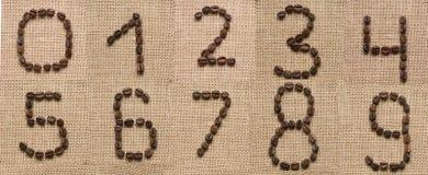 Нумерует коллаж от кофейных зерен на предпосылке мешковины стоковые изображения