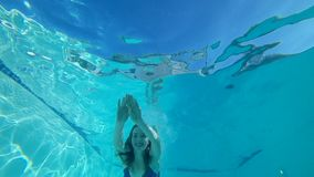 Ныряющ, усмехаясь женщина в купальник плавает под воду с открытыми глазами в чисто плавательном бассеине видеоматериал