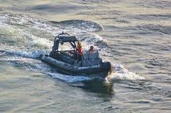 Ньюкасл, Великобритания - 5-ое октября 2014 - сторожевой катер НЕРВЮРЫ силы границы Великобритании с членом команды Стоковое Фото