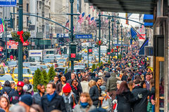 НЬЮ-ЙОРК, НЬЮ-ЙОРК - 30-ОЕ ДЕКАБРЯ 2013: Много туристских людей в Нью-Йорке, Манхаттане 5-ый бульвар Стоковое Фото