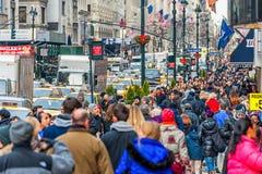 НЬЮ-ЙОРК, НЬЮ-ЙОРК - 30-ОЕ ДЕКАБРЯ 2013: Много туристских людей в Нью-Йорке, Манхаттане 5-ый бульвар Стоковое Изображение