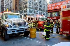НЬЮ-ЙОРК - 15-ое июня 2018: Отделения пожарной охраны нагнетают топливо от автомобиля после аварии Стоковые Изображения