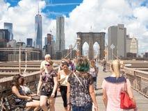 НЬЮ-ЙОРК, США 19,2015 -ГО АВГУСТ: Locals и туристы пересекая Бруклинский мост на красивом dayPeople лета пересекая ручеек Стоковые Фотографии RF