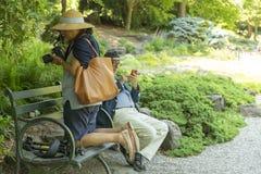НЬЮ-ЙОРК, США - 26-ОЕ ИЮНЯ 2018: Старшая взрослая отправка SMS и женщина человека принимая фото с камерой dslr стоковое изображение