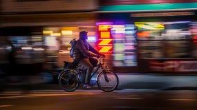 НЬЮ-ЙОРК, США - 18-ОЕ МАРТА 2018: Ехать велосипедисты Bicyclistsin в городе, ночи, конспекте запачканное движение стоковое изображение