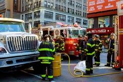 НЬЮ-ЙОРК - JJujy 02, 2018: Отделения пожарной охраны нагнетают топливо от автомобиля после аварии Стоковые Изображения RF