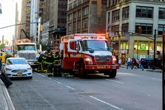 НЬЮ-ЙОРК - Jujy 02, 2018: Отделения пожарной охраны нагнетают топливо от автомобиля после аварии Стоковое Фото