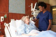 Нюна говоря к старшему женскому пациенту в больничной койке Стоковое Изображение RF