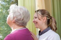 Нюна и старуха стоя на окне стоковое фото