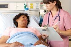 Нюна навещая старший женский пациент на палате стоковая фотография rf