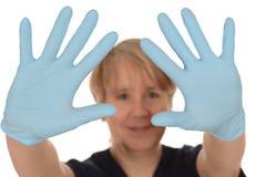 Нюна показывая голубые перчатки латекса стоковая фотография