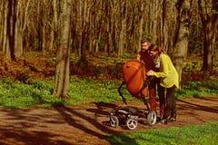Няни идут с pram младенца в парке Няни женщины и человека позаботятся о меньший ребенок Ответственность и стоковые фото