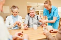 Нянча дама заботит для старшиев пока выпивающ кофе стоковая фотография rf