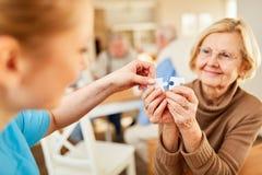Нянча дама помогает слабоумной пожилой женщине стоковое фото