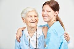 Нянча помощь и счастливая старшая женщина обнимая один другого Стоковые Фото