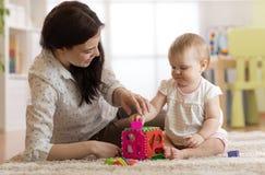 Няня и младенец играя с игрушками в питомнике стоковое фото
