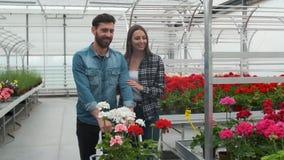 Нoung pary kupienia kwiaty w Nasłonecznionym ogródzie Robią zakupy 4K Coupe zakupy dla dekoracyjnych rośliien na pogodny florysty zbiory