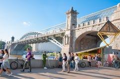 Обваловка Pushkin вполне людей вокруг Neskuchny садовничает с мостом Pushkin Andreevsky пешеходным через реку Москвы стоковое фото