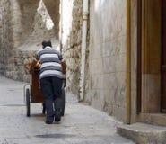 Обваляйте поставщика в сухарях нажимая его тележку в проходе христианского квартала, Иерусалима, Израиля Стоковые Фотографии RF