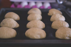 Обваляйте сформированное тесто в сухарях плюшек и подготавливайте для печь в печи Стоковое Изображение RF
