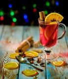Обдумыванное вино со специями на деревянном столе и гирлянде стоковые фотографии rf