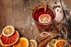 Обдумыванное вино, специи и высушенные плоды на деревенской таблице стоковое фото