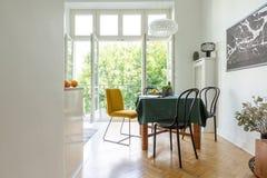 Обедать стулья вокруг деревянного стола на поле шевронного партера белой кухни с открытым балконом стоковые изображения rf