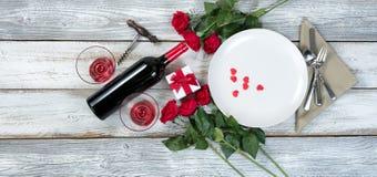 Обедающий валентинки с вином и розами на деревенском деревянном столе Стоковые Изображения RF