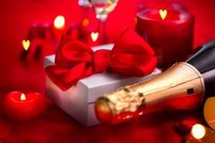 Обедающий дня валентинок романтичный дата Шампань, свечи и подарочная коробка над предпосылкой красного цвета праздника Стоковое Фото