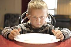 Обедающий расстроенного мальчика ждать пока держащ вилку и ложку стоковые изображения rf