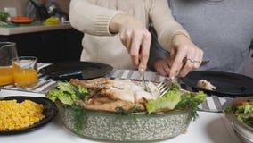 Обедающий семьи молодая пара в кухне Близко вверх, части отрезков женщины испеченного цыпленка и положения на плитах  видеоматериал