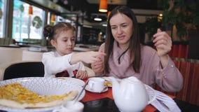 Обедающий семьи на пиццерии Мать и дочь в ресторане есть пиццу сток-видео