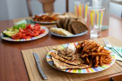 Обеденный стол с блюдом салата, цыпленком, сладкими картофелями, хлебом и красочным стеклом воды стоковая фотография