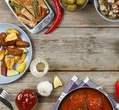 Обеденный стол с разнообразие едами и закусками Фрикадельки, испеченная картошка заклинивают, мясо, грибы, кетчуп Деревенский тип Стоковые Изображения RF