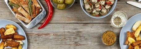 Обеденный стол с разнообразие едами и закусками Фрикадельки, испеченная картошка заклинивают, мясо, грибы, кетчуп Деревенский тип Стоковое Изображение RF
