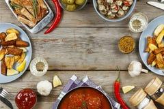 Обеденный стол с разнообразие едами и закусками Фрикадельки, испеченная картошка заклинивают, мясо, грибы, кетчуп Деревенский тип Стоковые Изображения