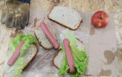 Обед ` s построителя, деревянная таблица работы на строительной площадке с едой и инструменты построителя Стоковая Фотография RF