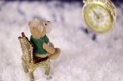 Обезьяна плюша на стуле смотря часы нет в фокусе Стоковая Фотография RF