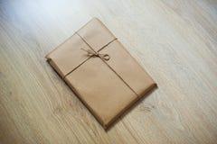 Обернутая бумага kraft подарка на деревянной предпосылке Стоковое Фото
