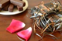 Обернутая подарочная коробка на коричневых лепестках розы и помадках таблицы Стоковые Фотографии RF