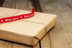 Обернутая подарочная коробка с красной лентой Стоковое Изображение