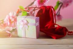 Обернутые подарочная коробка и красная сумка подарка и настоящие моменты рождества и Newyear цветения сливы с смычками и лентами, Стоковое Изображение