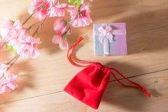 Обернутые подарочная коробка и красная сумка подарка и настоящие моменты рождества и Newyear цветения сливы с смычками и лентами, Стоковое Фото