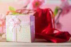 Обернутые подарочная коробка и красная сумка подарка и настоящие моменты рождества и Newyear цветения сливы с смычками и лентами, Стоковое фото RF
