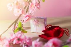 Обернутые подарочная коробка и красная сумка подарка и настоящие моменты рождества и Newyear цветения сливы с смычками и лентами, Стоковые Фотографии RF