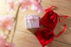 Обернутые подарочная коробка и красная сумка подарка и настоящие моменты рождества и Newyear цветения сливы с смычками и лентами, Стоковая Фотография